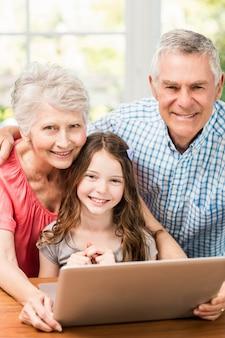 Retrato de sonrientes abuelos y nieta usando laptop en casa