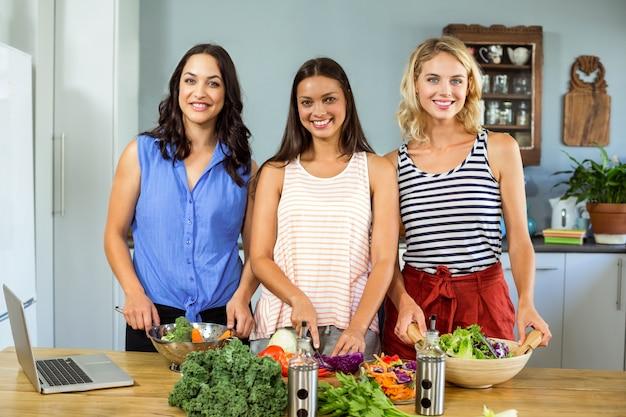 Retrato de sonrientes amigas preparando la comida en la cocina