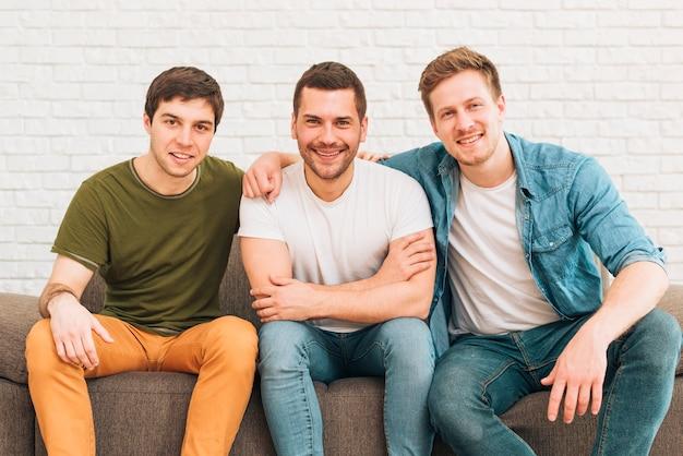 Retrato de sonrientes amigos varones sentados juntos en el sofá