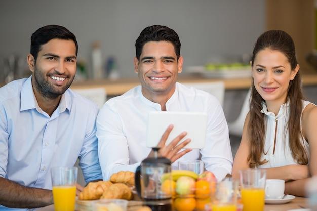 Retrato de sonrientes colegas desayunando juntos