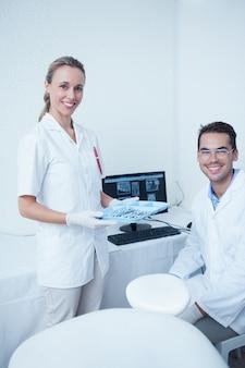 Retrato de sonrientes dentistas con monitor de la computadora