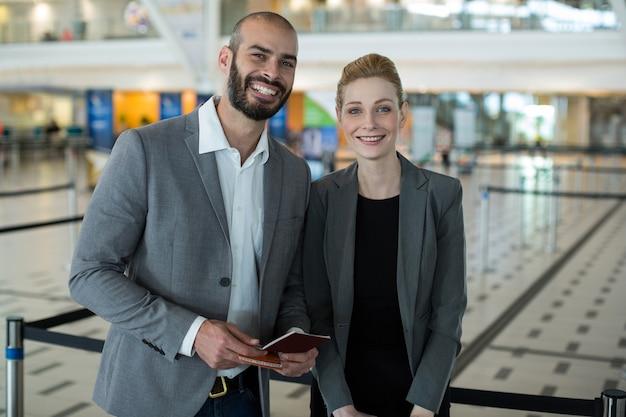 Retrato de sonrientes empresarios con pasaporte esperando en cola