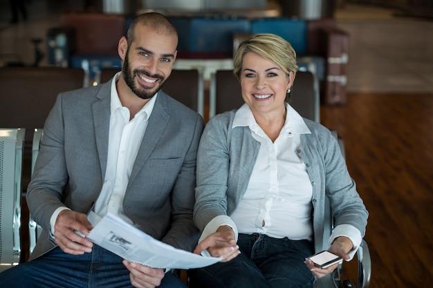 Retrato de sonrientes empresarios sentados en la sala de espera con periódico
