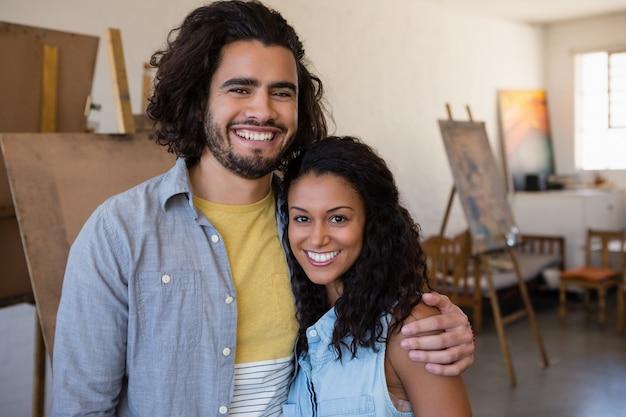 Retrato de sonrientes estudiantes adultos con brazo alrededor