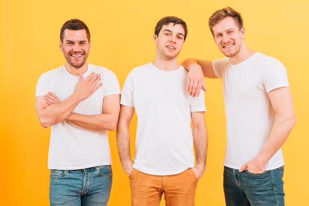 Retrato de sonrientes tres amigos varones en camiseta blanca mirando a cámara