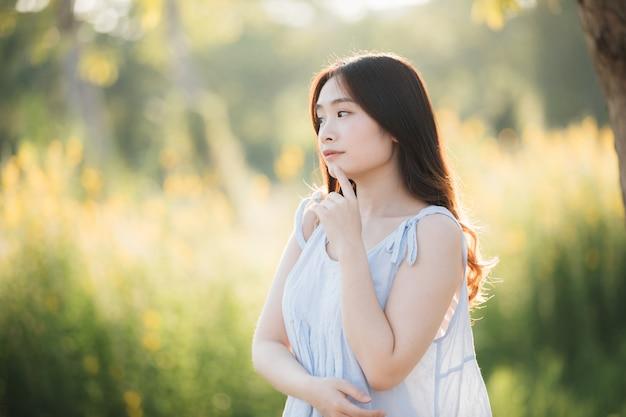 Retrato de la sonrisa asiática joven de la muchacha de la mujer en jardín de flores