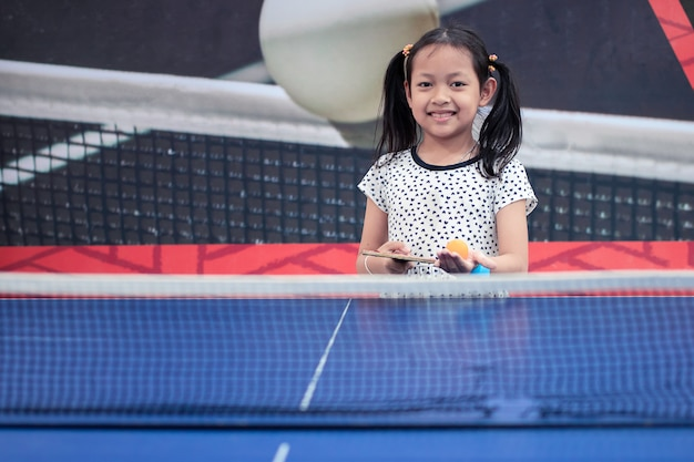 Retrato de sonrisa asiática niña jugar tenis de mesa