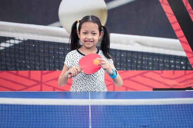 Retrato de la sonrisa chica asiática jugar tenis de mesa