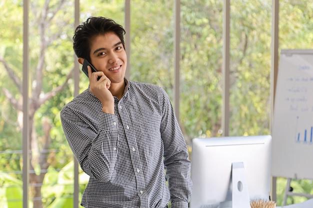 Retrato de sonrisa inteligente joven empresario asiático hacer una llamada telefónica y sentirse feliz con el teléfono móvil inteligente