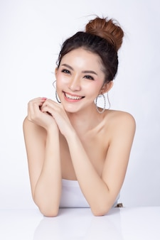 Retrato de la sonrisa que se sienta de la mujer asiática atractiva en el fondo blanco.