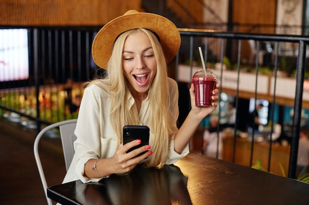 Retrato de sorprendida dama rubia de pelo largo con sombrero ancho marrón y camisa blanca sentada en el restaurante durante el almuerzo, bebiendo batido y revisando las redes sociales en su teléfono móvil