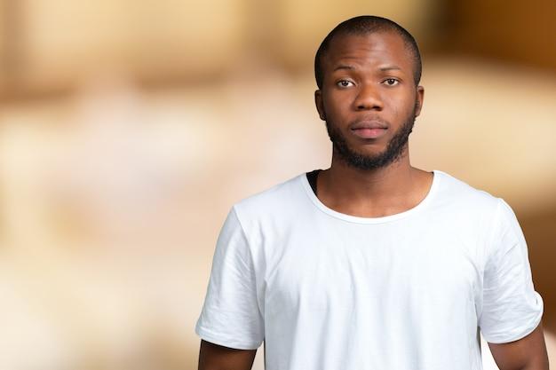 Retrato de stong y guapo estudiante masculino africano mirando a la cámara sonriendo