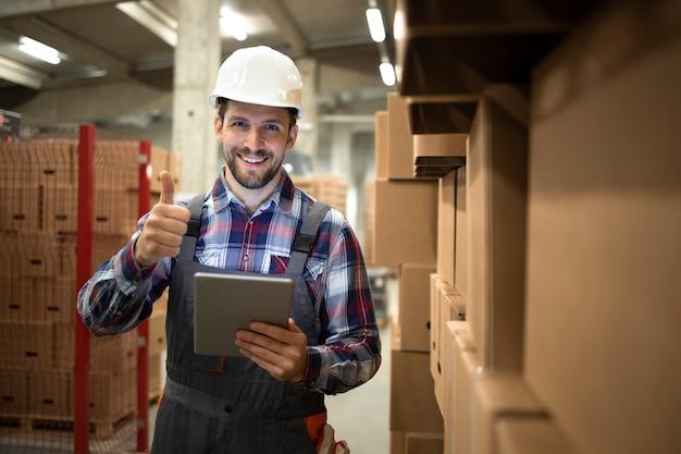 Retrato de supervisor de almacén que organiza con éxito la distribución y el envío de mercancías desde una gran sala de almacenamiento al mercado.