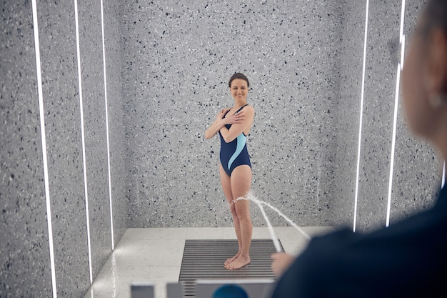 Retrato de tamaño completo de una paciente con los brazos cruzados de pie durante el procedimiento de hidroterapia