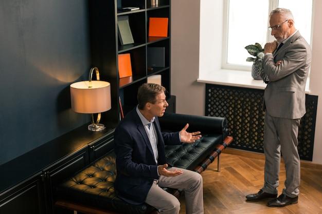 Retrato de tamaño completo de un psiquiatra caucásico serio escuchando a su paciente preocupado mientras está de pie junto a él