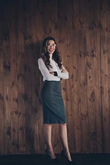Retrato de tamaño de cuerpo completo vertical de agradable atractivo encantador ajuste delgado alegre dama de cabello ondulado abogado abogado fundador de la empresa desarrollador lugar de trabajo estación sobre pared de madera
