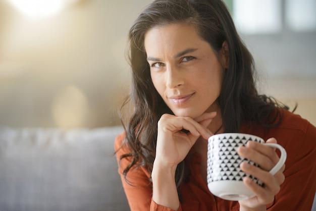 Retrato del té de consumición de la mujer morena atractiva