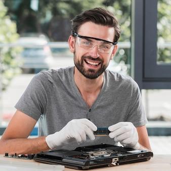 Retrato de un técnico de sexo masculino joven sonriente que sostiene el ordenador portátil ram