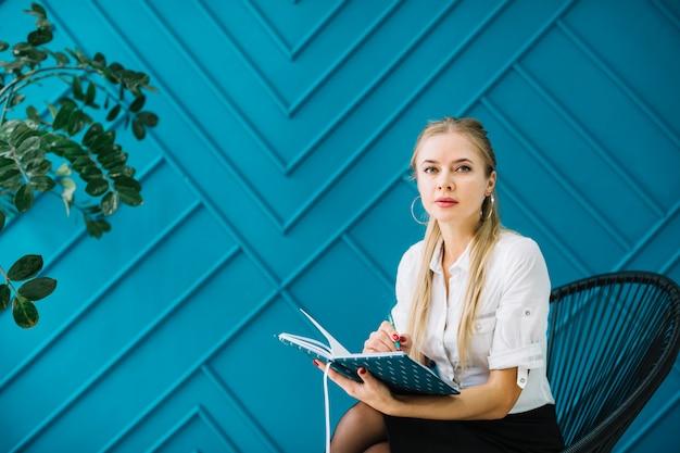 Retrato de terapeuta feliz con notas sentado contra la pared de diseño azul