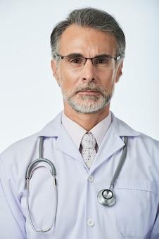 Retrato de terapeuta profesional experimentado con estetoscopio mirando a cámara