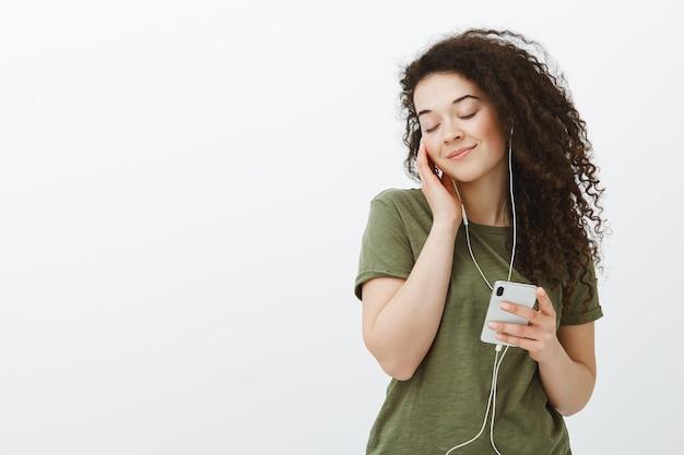 Retrato de tierna hermosa mujer morena de pelo rizado en traje casual, cerrando los ojos y sonriendo felizmente, escuchando música en auriculares y sosteniendo un teléfono inteligente