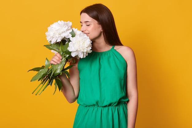 Retrato de tierna mujer adorable con flores blancas en una mano
