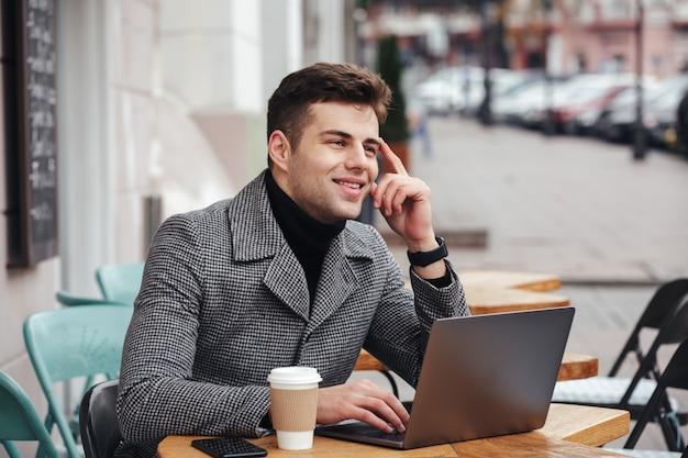 Retrato de un tipo exitoso que trabaja con una computadora portátil plateada en un café callejero, piensa en negocios o chatea con un amigo