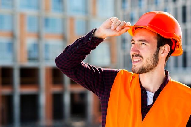 Retrato del tiro medio del trabajador de construcción que mira lejos