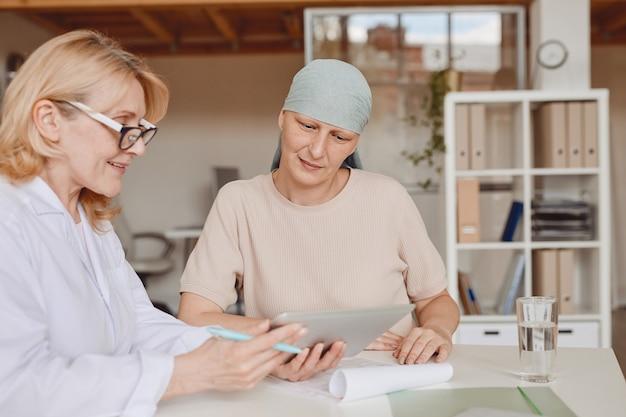 Retrato de tonos cálidos de mujer calva madura escuchando a la doctora mostrando información en tableta digital durante la consulta sobre alopecia y recuperación del cáncer, espacio de copia