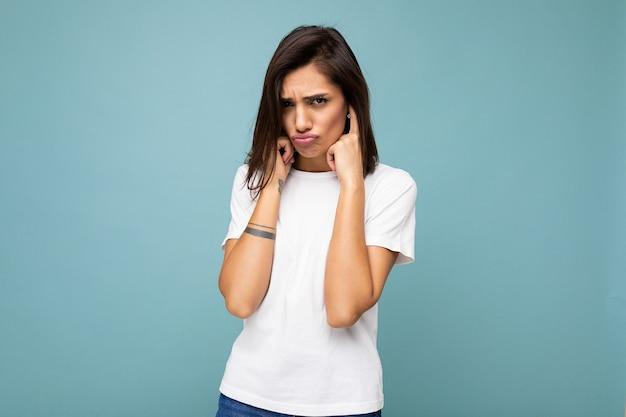 Retrato de touchu triste tristeza joven hermosa mujer morena con emociones sinceras vistiendo casual camiseta blanca para maqueta aislado en superficie azul con espacio vacío yc