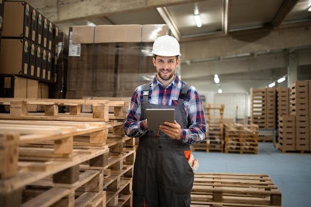 Retrato de trabajador de almacén escribiendo en tablet pc y de pie junto a la paleta de madera en la sala de almacenamiento de la fábrica.