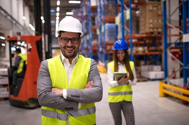 Retrato de trabajador de almacén exitoso o supervisor con los brazos cruzados de pie en una gran área de distribución de almacenamiento