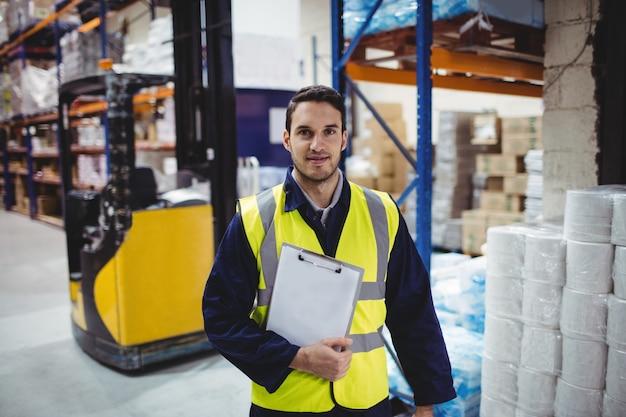 Retrato de trabajador de almacén con portapapeles en almacén