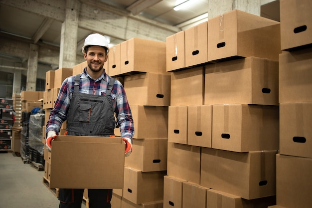 Retrato de trabajador de almacén en ropa de trabajo y casco con caja de cartón reubicar mercancías en el almacenamiento de la fábrica.