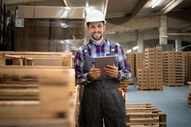 Retrato de trabajador de almacén con tablet pc y de pie junto a la paleta de madera en la sala de almacenamiento de la fábrica.