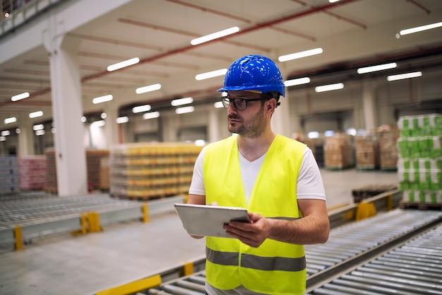 Retrato de trabajador de almacén con tableta de pie en el departamento de almacenamiento