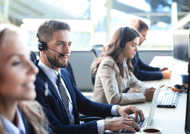 Retrato de trabajador de call center acompañado de su equipo. operador de soporte al cliente sonriente en el trabajo.