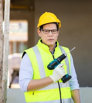 Retrato de trabajador de capataz de construcción en casco de seguridad casco de perforación con taladro eléctrico en el sitio de construcción