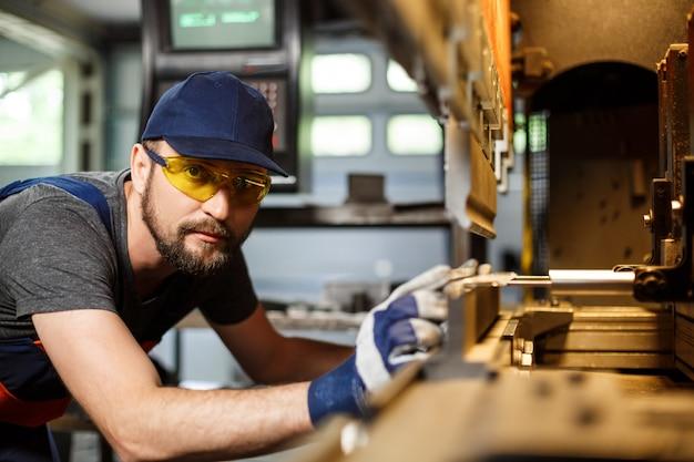 Retrato de trabajador cerca de la máquina metalúrgica