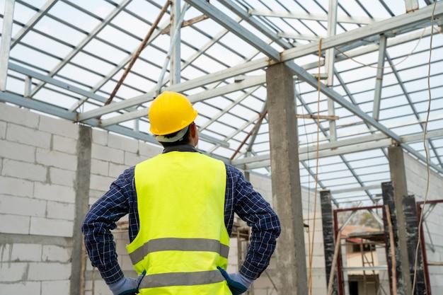 Retrato de trabajador de la construcción en obra, trabajador de la construcción con casco trabajando en casa nueva.