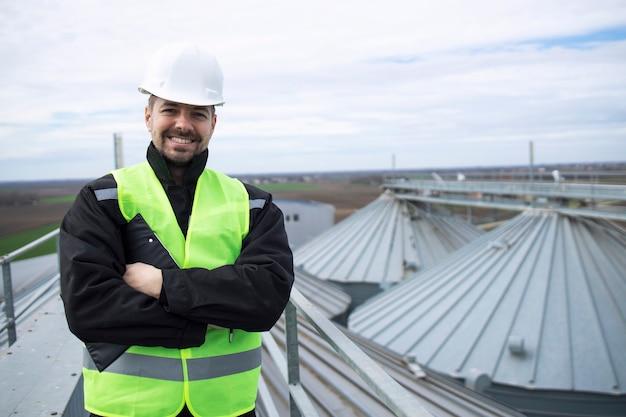 Retrato de trabajador de la construcción de pie sobre los tejados de tanques de almacenamiento de silos altos