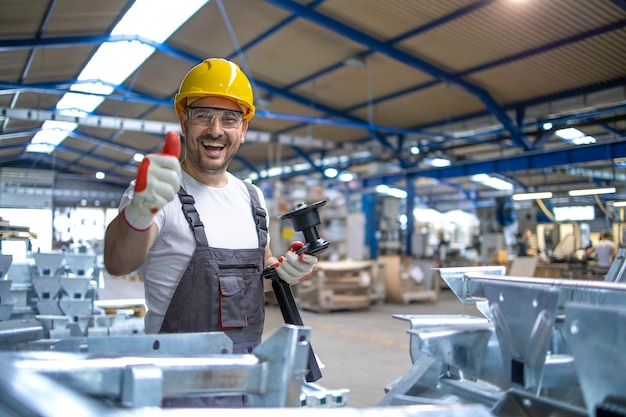 Retrato de trabajador de fábrica en equipo de protección sosteniendo thumbs up en la sala de producción