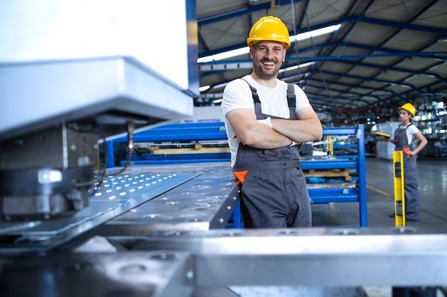 Retrato de trabajador de fábrica en uniforme protector y casco permanente por máquina industrial en la línea de producción