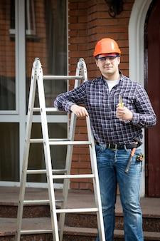 Retrato de trabajador feliz en sitio de construcción sosteniendo thumbs up