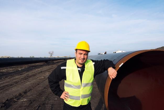 Retrato de un trabajador industrial de pie junto a la tubería de gas en el sitio de construcción