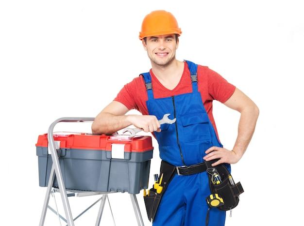 Retrato de trabajador manual sonriente con herramientas aisladas en blanco