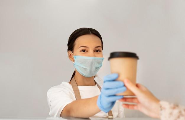 Retrato de trabajador con mascarilla y guantes quirúrgicos