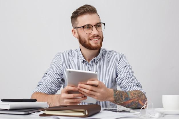 Retrato de trabajador de oficina exitoso en gafas redondas, tiene brazos tatuados, sostiene tableta moderna
