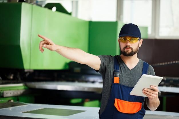 Retrato del trabajador que señala el dedo en el lado, fondo de la fábrica de acero.