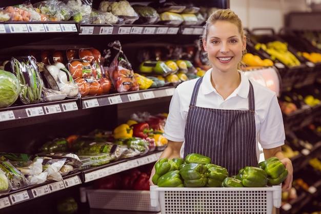 Retrato de un trabajador rubio sonriente que sostiene verduras